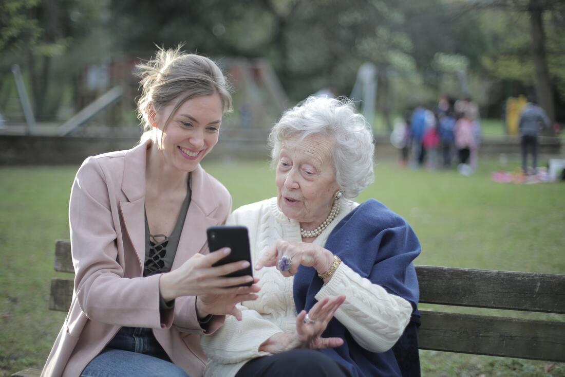 Two people from different generations sit smiling and talking on a park bench looking at a phone