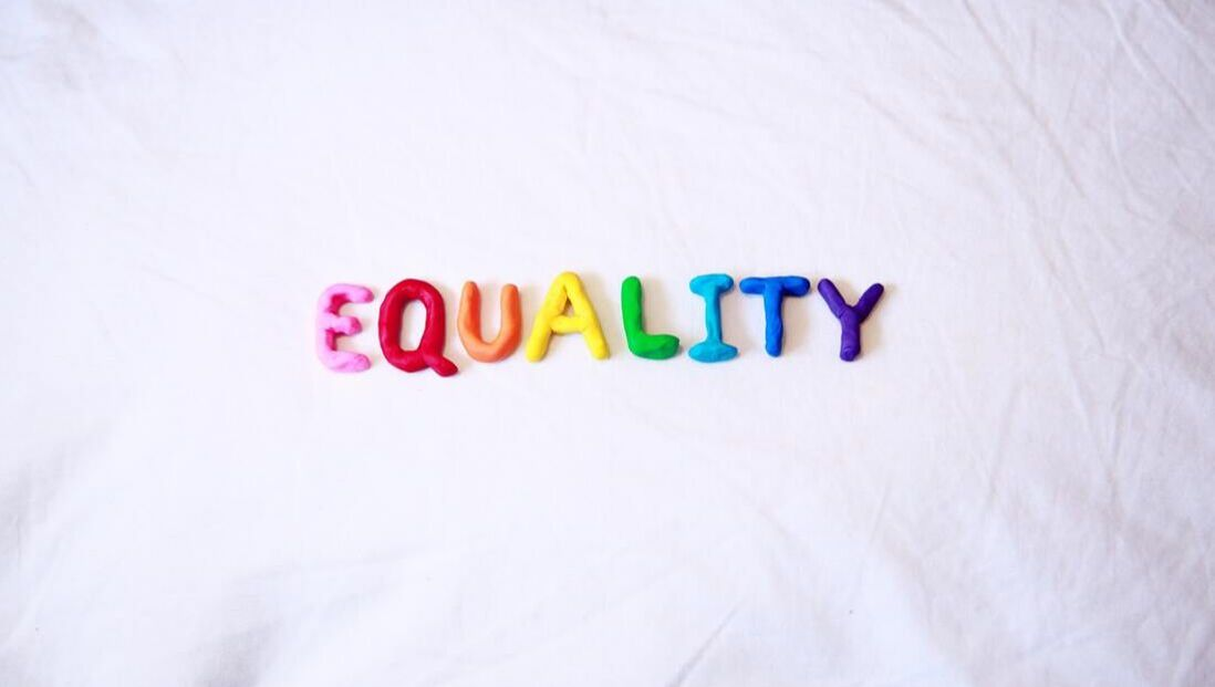 The word Equality is spelled out in rainbow letters on a white background.