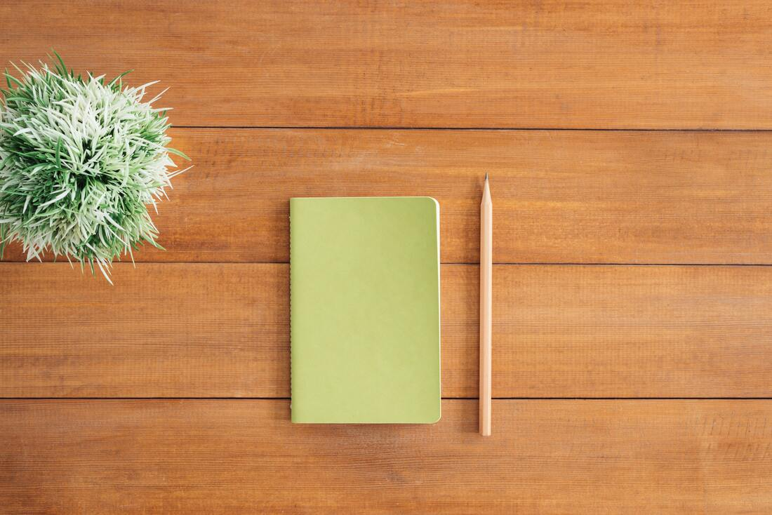 Green notebook and a plain wooden pencil