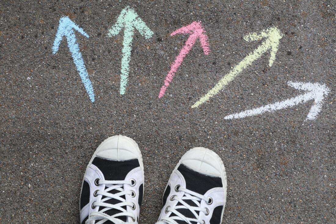 Five coloured chalk arrows (blue, green, pink, yellow and white) pointing in different directions on pavement in front of a pair of shoes.